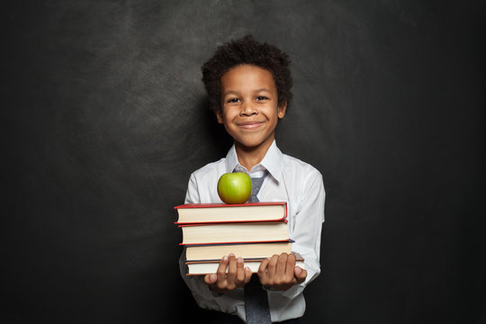 Happy black child student holding books and apple and smiling on chalkboard background