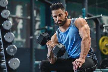 Handsome bodybuilder picking up dumbbells at gym