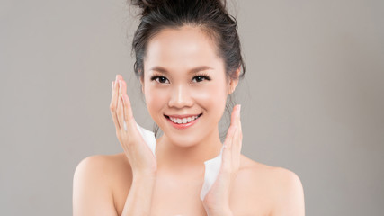 Asian women are going to use a facial foam to wash cosmetics off the face.white backgrond