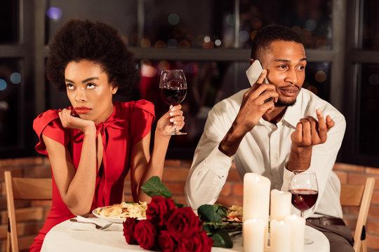 Bored Girl Having Dinner With Boyfriend Sitting In Restaurant
