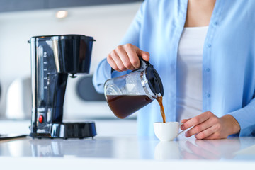 Woman using coffee maker for making and brewing coffee at home. Coffee blender and household...