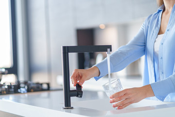 Woman pours fresh filtered purified water from a tap into a glass at kitchen at home for drinking