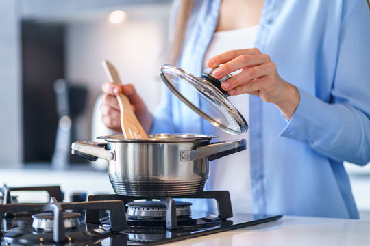 Woman housewife using steel metallic saucepan for preparing dinner in the kitchen at home. Kitchenware for cooking