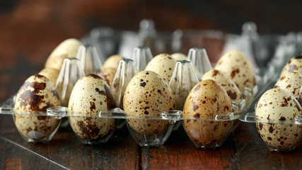 Quail eggs in transparent plastic container on wooden table