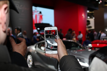 FRANKFURT, GERMANY - SEP 23, 2017: Apple iPhone 6S. Smartphone with video mode. - mobile screen / display. - visitors look at the Ferrari model 812 Superfast. International Automobile Exhibition IAA.