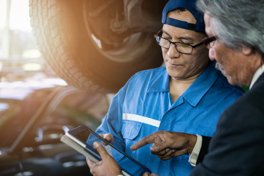 car mechanic talking with service station manager about car maintenance list show in service tablet