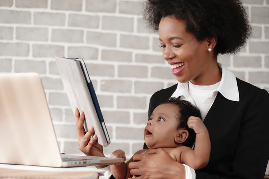 african american mother holding her baby boy on hands while working with laptop computer at home