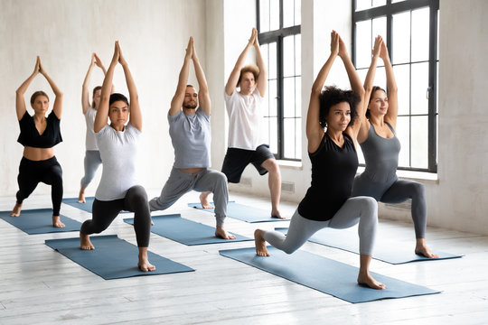 Young diverse people doing Warrior one exercise, practicing yoga
