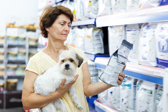 Glad woman choosing dog food for her puppy