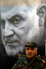 A Syrian military personnel sits past a picture of late Iranian Major-General Qassem Soleimani, head of the elite Quds Force, during a memorial service for him at the Iranian embassy in Damascus