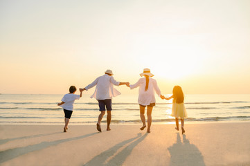 Family, travel, beach, relax, lifestyle, holiday concept. Family who enjoy a picnic. Parents are holding hands their children and walking on the beach at sunset in holiday.