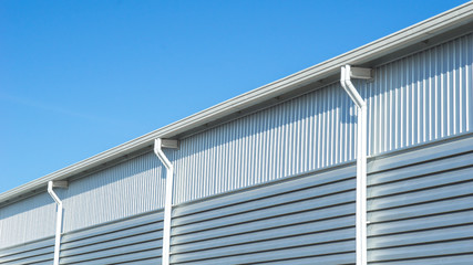 Close up wall and roof of Factory or warehouse building in industrial estate with blue sky and copyspace