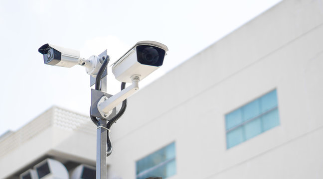CCTV surveillance security camera video equipment on pole outdoor building safety system area control and copy space