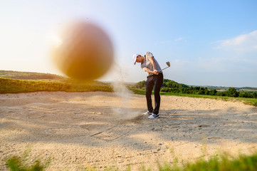 lifestyle, golf, activity, outdoor, sport, golfer concept. A close-up golf ball blurred by man is sweeping golf on the sand at a golf course in the summer. Sport lifestyle Concept. Bright picture.
