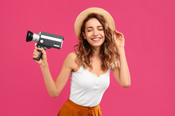 Beautiful young woman with vintage video camera on crimson background