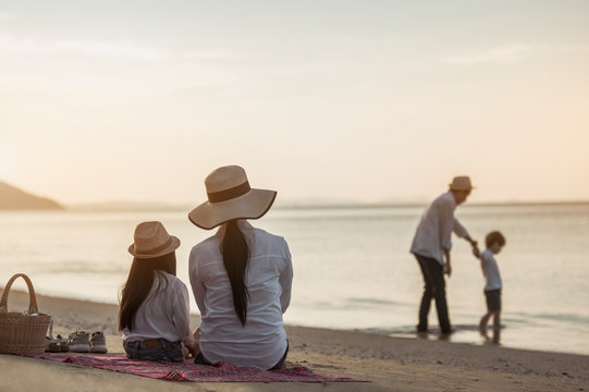 Family, travel, beach, relax, lifestyle, holiday concept. Parents and children who enjoy a picnic at the beach on sunset in holiday.