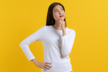 Cute asian young woman in white casual dress looking up and thinking / imagination isolated on yellow background in studio.