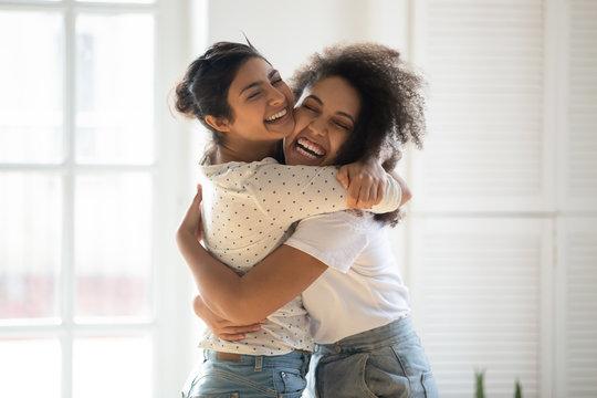 Happy multiethnic girlfriends have fun hugging indoors