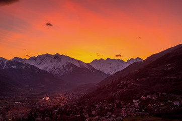Panorama of Aosta city at sunset, with mountains on background and colorfull sky