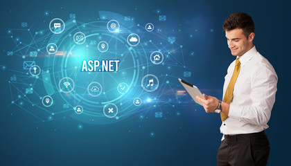 Businessman thinking in front of technology related icons and ASP.NET inscription, modern...