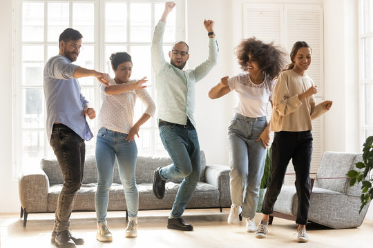 Overjoyed multiracial young people dancing together indoors