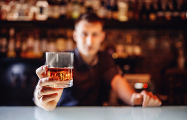 Barman holds out glass of whiskey with ice to male visitor. Concept rest in bar