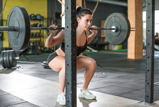 Photo of a woman is lifting weight while working out with barbell in gym.