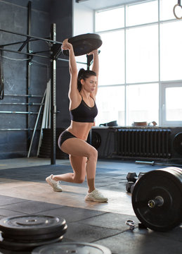 Close up front portriat of a woman is lifting weight while working out in gym.
