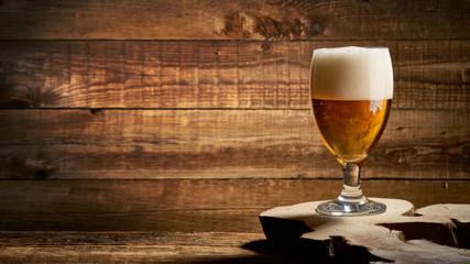Obraz Spienione piwo w szklance na starych deskach - fototapety do salonu