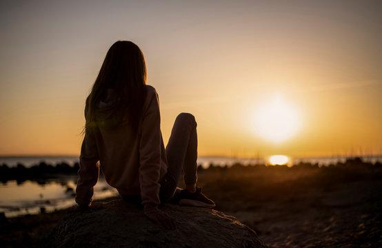 Mädchen genießt den Sonnenuntergang am Meer