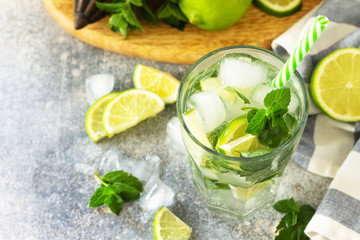 Fresh Mojito cocktail with lime, ice and mint in a glass on a gray stone background. Summer cold...