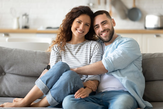 Portrait of couple posing photo shooting seated on couch indoors