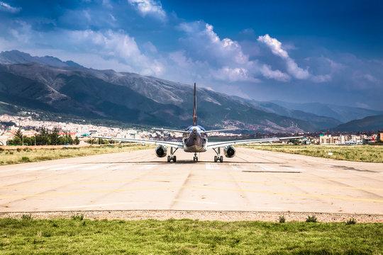 Modern passenger plane at airport lane moving to take off , Cusco , Peru.