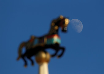 The waxing gibbous moon is seen behind a sculpture of a horse on top of a carousel at a Christmas fair in Valletta