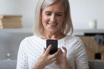 Modern elderly woman using smartphone browsing internet