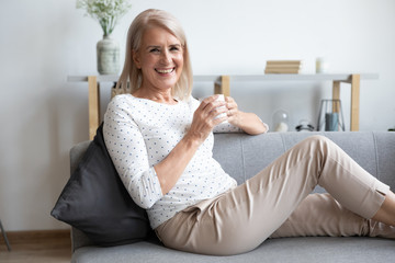 Photo sur Aluminium Individuel Portrait of smiling mature woman relaxing on couch with cup