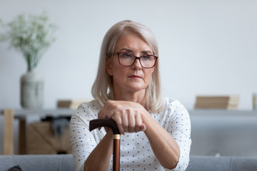 Sad senior woman hold walking cane feeling lonely at home
