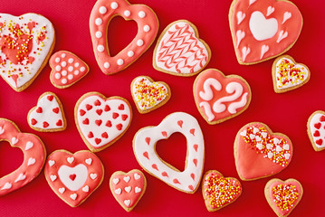 Background of decorated with icing and glazed heart shape cookies on the red background, flat lay. Valentines Day food concept