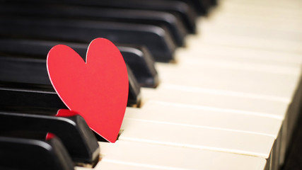 Small red paper heart on piano keys. Concept of love, valentine's day. Toned in warm color