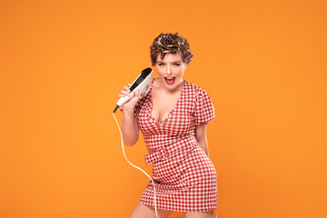 Pinup girl posing with retro dryer.