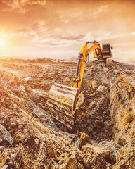 Excavator stands on construction site at sunset
