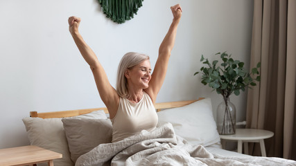 Smiling elderly woman stretching in bed welcoming new day