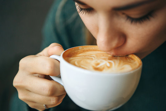 Close up girl is drinking coffee. She enjoys her morning cappuccino or flat white.