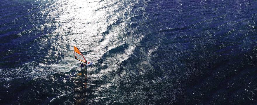 Aerial drone ultra wide photo of wind athlete surfer practising in deep blue open ocean sea