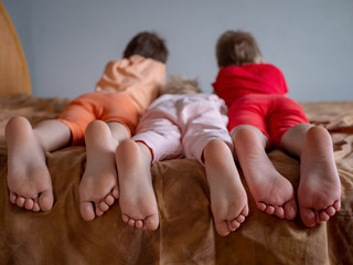 Three brother boys were lying on couch and were busy with phone and tablet. boys are wearing barefoot home pajamas. Feet and toes closeup. Tender baby feet