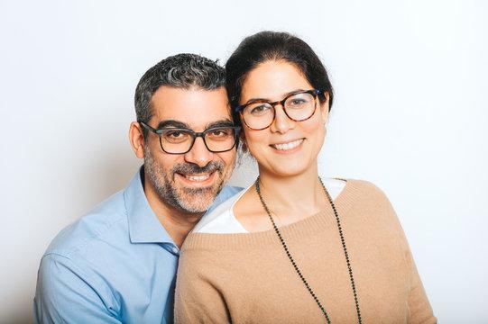 Studio portrait of happy couple wearing eyeglasses, posing together on white background