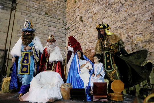 Men dressed up as Gaspar, Melchior, and Balthasar, the Three Wise Men, stand next to people dressed up as Mary, Joseph and the baby Jesus replicating the Nativity scene during the Epiphany parade in Ronda