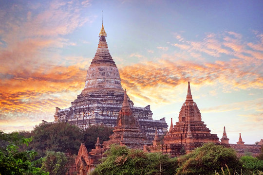 Colorful sunset sky above temples surrounded by green vegetation in old Bagan, Myanmar.