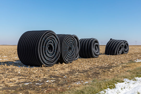 Coiled rolls of black perforated plastic drainage pipe, field tile, sitting in farm field after harvest ready to be buried underground during winter