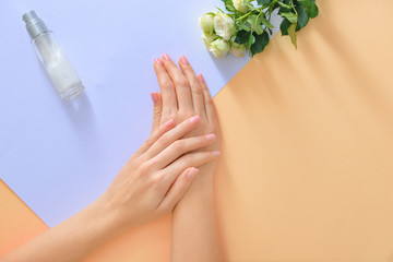 Hands of young woman and bottle of cream with flowers on color background